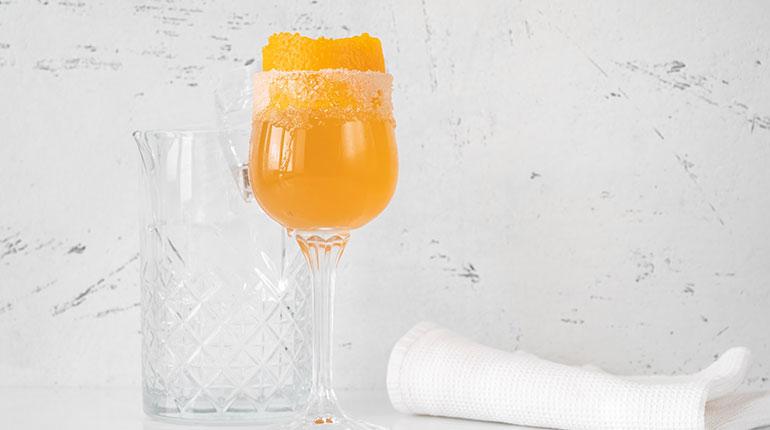 Portakal kabuğu ile süslenmiş bir bardak Brandy Crusta kokteyli